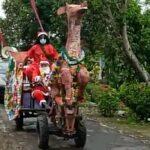 """Natal 2020, Naik """"Kereta Rusa"""" Sinterklas Bagikan Bingkisan ke Rumah Warga di Jember"""